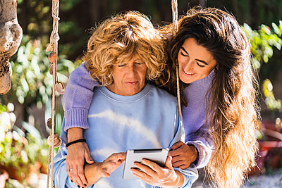 Smiling daughter standing with arm around on mother using digital tablet while sitting on swing - p300m2276087 by Manu Padilla Photo