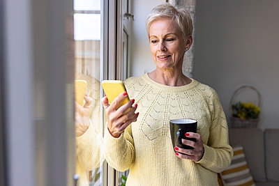 Mature woman using smart phone while holding mug at home - p300m2294248 by William Perugini