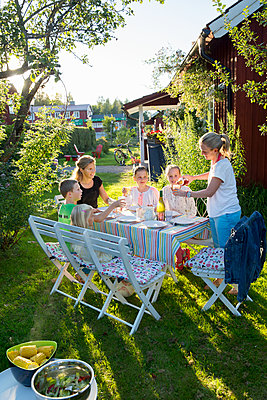 Family having meal in garden - p312m1498950 by Lena Granefelt