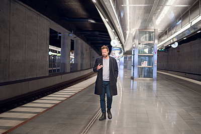 Young man at metro station - p312m2080617 by Viktor Holm