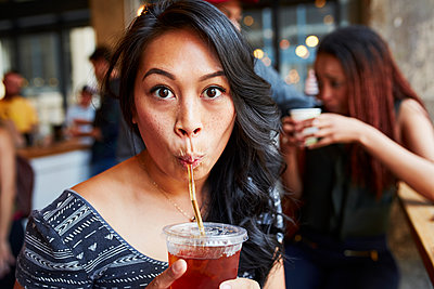 Woman drinking cold drink with straw in cafe - p555m1305446 by Granger Wootz