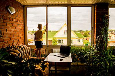 Caucasian boy looking out living room window - p555m1411167 by Aleksander Rubtsov