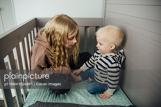 Girl with brother sitting in crib at home - p1166m1524661 by Cavan Images