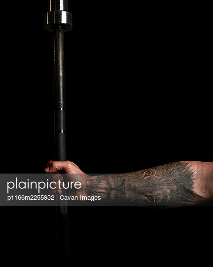 man hand with tattoo holding barbell weightlifting with black studio background - p1166m2255932 by Cavan Images