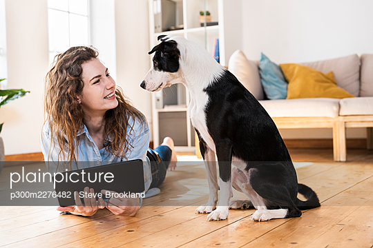 Happy woman with digital tablet looking at dog while lying on floor in living room - p300m2276482 by Steve Brookland