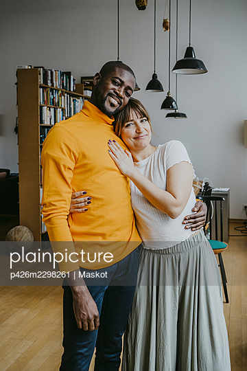 Portrait of smiling couple standing with arm around at home - p426m2298261 by Maskot