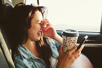 Happy woman with coffee cup using mobile phone while traveling in car - p1166m1423042 by Cavan Images