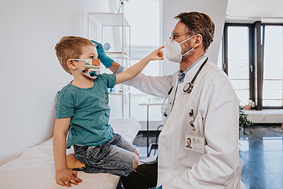 Male pediatrician with protective face mask checking boy in medical examination room - p300m2267688 by Mareen Fischinger
