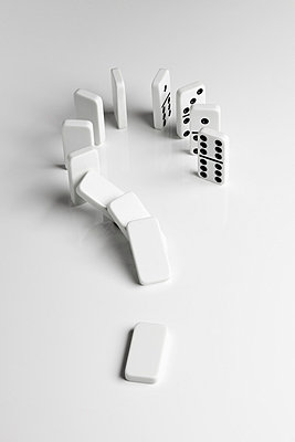 Dominoes arranged in a question mark falling over in a chain reaction - p301m730800f by Larry Washburn
