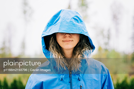 woman standing in the rain with her hood over her eyes - p1166m2193796 by Cavan Images