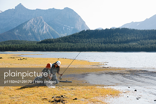 Mother and son fishing at scenic, sunny lakeside - p1192m2129170 by Hero Images