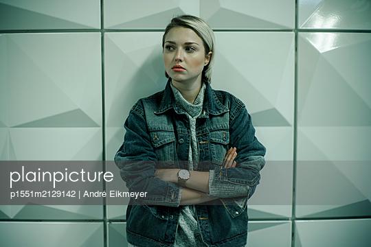 Junge blonde Frau lehnt an Wand mit geometrischem Muster - p1551m2129142 von André Eikmeyer