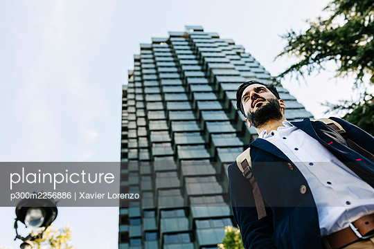 Mid adult businessman looking away while standing in city - p300m2256886 by Xavier Lorenzo