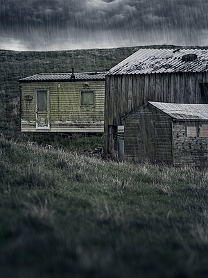 Great Britain, Old mobile home on farm with buildings in the rain - p1280m2232000 by Dave Wall