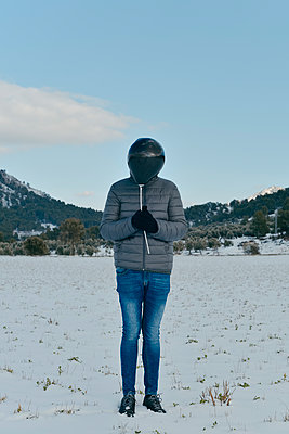 Man on the snow holding a black balloon in front of his face - p1423m2279929 by JUAN MOYANO