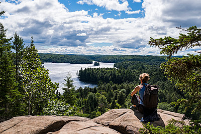 Junge Frau sitzt im Algonquin National Park in Kanada auf einem Felsen - p177m1214591 von Kirsten Nijhof