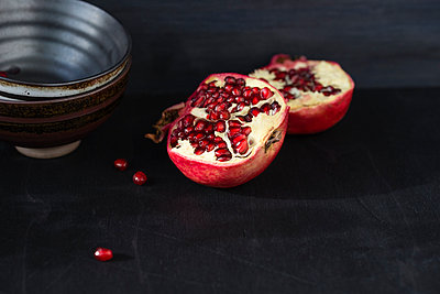 Bowl and two halves of a pomegranate on black ground - p300m978967f by Mandy Reschke