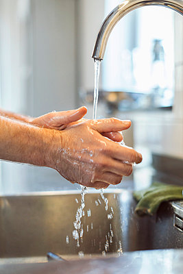 Cropped image of man washing hands in kitchen sink - p426m1017941f by Maskot