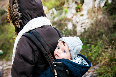 Portrait of baby boy wearing knit hat, carried in baby sling by mother - p429m1227246 by Bonfanti Diego