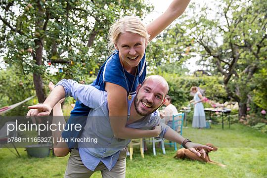 Junges Paar albert im Garten herum - p788m1165327 von Lisa Krechting
