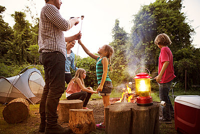 Daughter showing roasted marshmallow to father while enjoying with family at summer camp - p1166m1096940f by Cavan Images