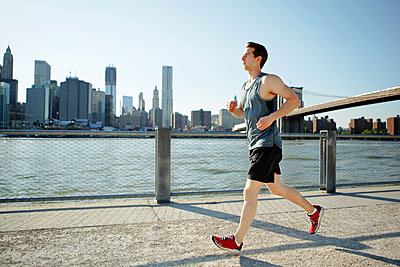 Side view of man jogging on pathway by East River against sky - p1166m1163484 by Cavan Images