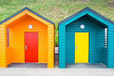 Two brightly coloured beach huts - p1302m1573488 by Richard Nixon