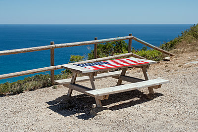 Flag of the United States on an outdoor picnic table, with the sea in the background - p1423m2196470 by JUAN MOYANO