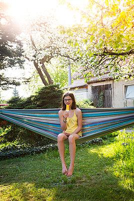 Smiling girl sitting on hammock in the garden eating ice lolly - p300m1588086 von Larissa Veronesi
