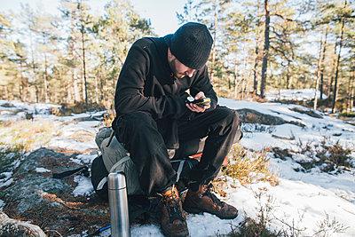 Sweden, Sodermanland, backpacker resting in remote landscape in winter using GPS tracker - p300m2005587 by Gustafsson