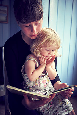 Mother reading book to her daughter - p312m1338531 by Dan Lepp