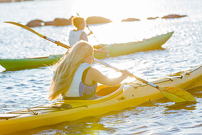 Women kayaking at evening - p312m992930f by Ulf Huett Nilsson