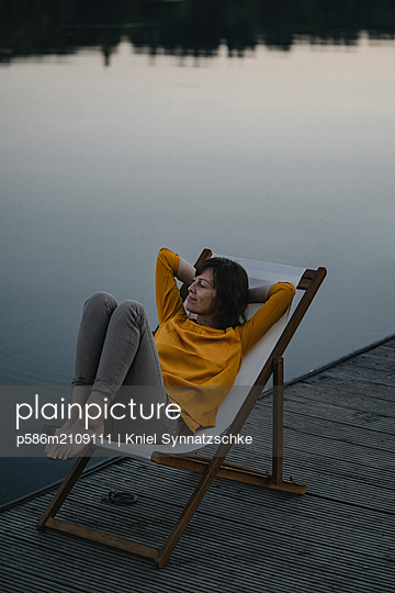 Mature woman in canvas chair on the lakefront - p586m2109111 by Kniel Synnatzschke