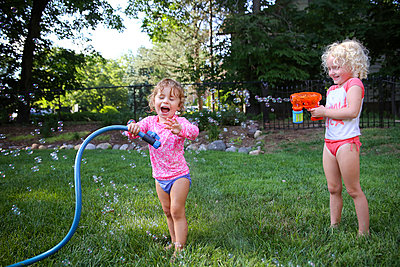 Happy sisters playing in backyard - p1166m1403815 by Cavan Images