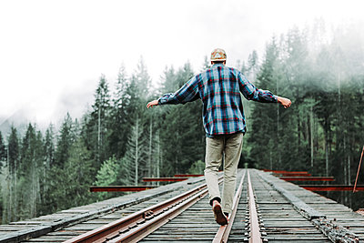 Young man balancing on railroad tracks over bridge in foggy forest - p1166m2162921 by Cavan Images