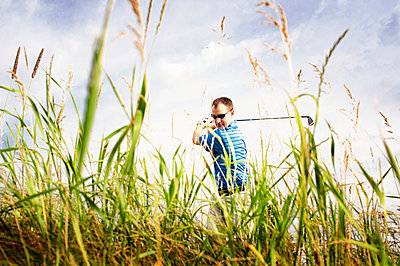 Confident man playing golf on field against sky - p1166m969517f by Cavan Images
