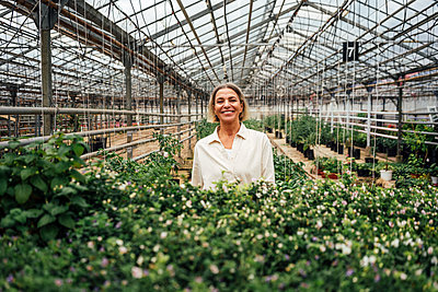 Smiling female farmer standing near plants in greenhouse - p300m2300022 by Vasily Pindyurin