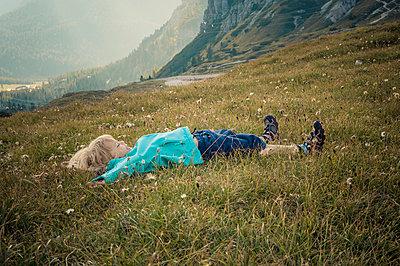 little boy lying on alpine meadow near Tre Cime di Lavaredo - p300m885089f by Jana Mänz