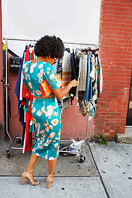 Rear view of young female fashion blogger with afro hair looking at sidewalk clothes rail, New York, USA - p924m1422628 by Karen E. Evans