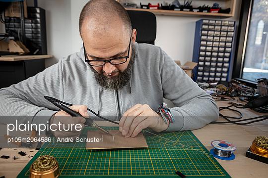Elektriker lötet Bauteile auf eine Platine - p105m2064586 von André Schuster