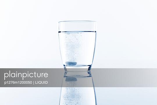 Glas Wasser mit einer sich auflösenden Tablette - p1276m1200050 von LIQUID