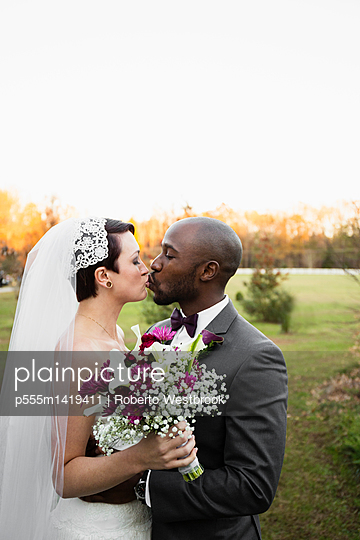 Newlywed couple kissing in park - p555m1419411 by Roberto Westbrook