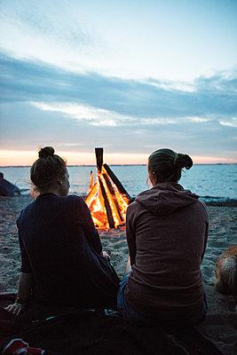 Freundinnen am Lagerfeuer am Strand - p1142m1362248 von Runar Lind