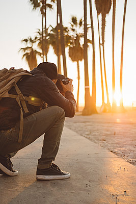 Man with backpack photographing beach against clear sky during sunset - p1166m1576449 by Cavan Images