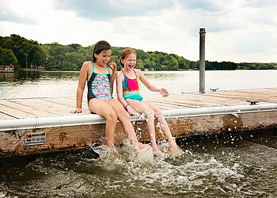 Two Young Girls in Swimsuits Sitting on a Dock by Lake Splashing Their - p1166m2153608 by Cavan Images