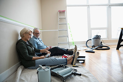 Senior couple preparing to paint in living room, looking at paint swatches, DIY - p1192m1560006 by Hero Images