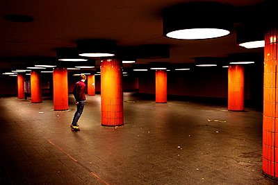 Einzelner Mann mit Skateboard in einer U-Bahnstation - p1268m1111497 von Mastahkid