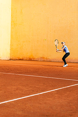 Teenage girl playing tennis on court - p300m1356497 by Valentina Barreto