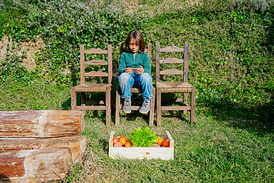 Boy sitting in garden with vegetable box, playing games on his smartphone - p300m2069856 by Gemma Ferrando
