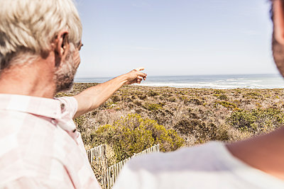 Two men at the sea looking at view - p300m2166964 by Floco Images